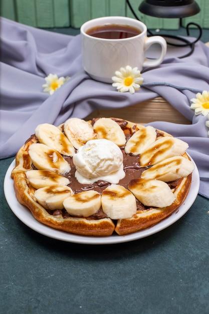 Gaufres Avec Banane Tranchée, Sauce Au Caramel Et Crème à Fouetter Avec Une Tasse De Thé Photo gratuit