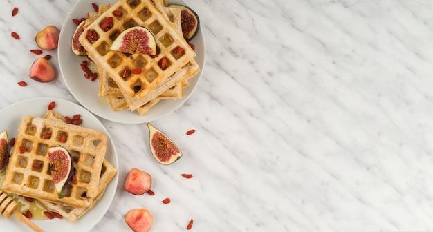 Des gaufres belges en bonne santé; figue; mon chéri; et louche de miel servis dans l'assiette contre le sol en marbre Photo gratuit