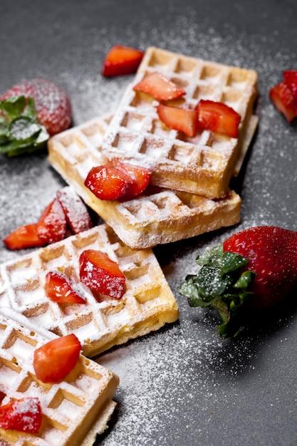 Gaufres belges avec des fraises et du sucre en poudre sur tableau noir. Photo Premium
