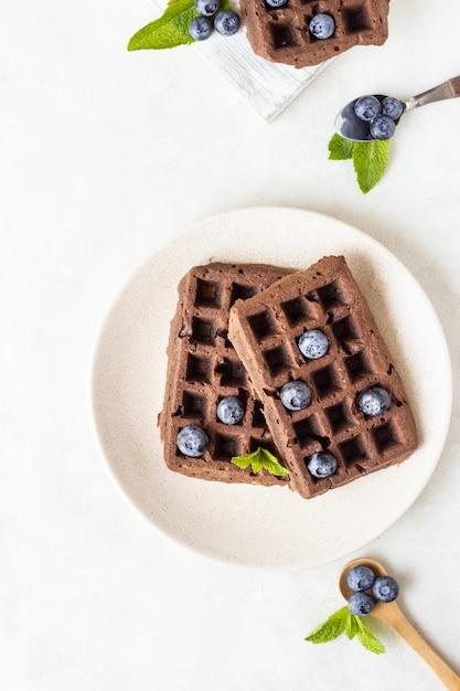 Gaufres bruxelloises au chocolat avec myrtilles et menthe sur une assiette. Photo Premium