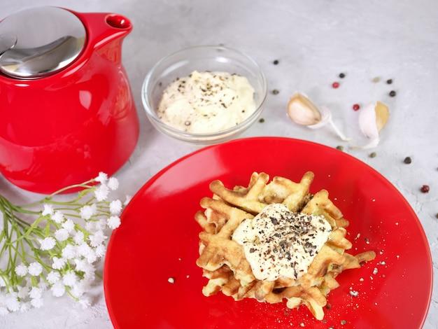 Gaufres de courgettes sur une assiette rouge avec sauce et épices, Photo Premium