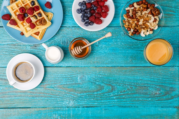 Gaufres faites maison, framboises et myrtilles fraîches, tasse de café, lait, noix et miel. Photo Premium