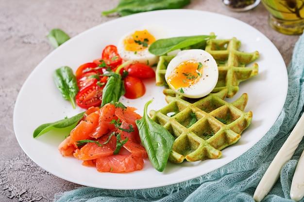 Gaufres salées avec des épinards et des œufs, tomates, saumon dans une assiette blanche. Photo Premium