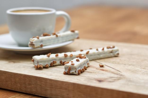 Gaufrettes de biscuit en glaçure et tasse de café sur une table en bois Photo Premium