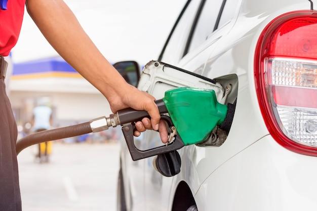 Gaz de pompage à la pompe à essence. gros plan d'un homme pompant de l'essence dans une voiture à la station d'essence Photo Premium