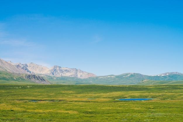 Géant Des Montagnes De Neige Au-dessus D'une Vallée Verdoyante Sous Un Ciel Bleu Clair. Prairie Avec Une Riche Végétation Et Des Lacs De Hautes Terres Au Soleil. Magnifique Paysage De Montagne Ensoleillé De Nature Majestueuse. Photo Premium