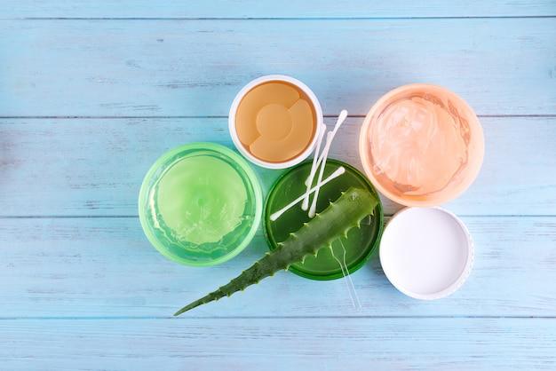Gel d'escargot, cache-oeil et gel d'aloe vera frais en pot sur fond en bois bleu Photo Premium