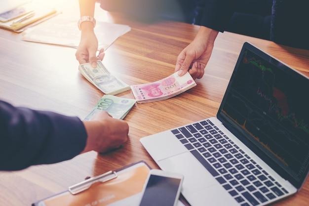 Les gens d'affaires détiennent le partage d'argent pour des investissements en échange Photo Premium