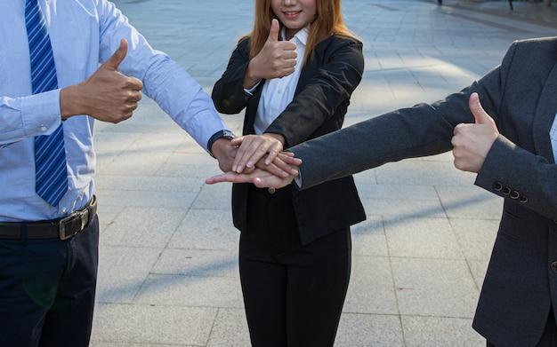 Gens d'affaires donner le pouce et empiler les mains dans le travail d'équipe. Photo Premium