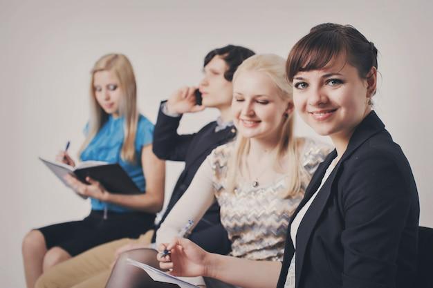 Gens d'affaires en file d'attente assis dans la rangée, tenant des smartphones et des cvs Photo Premium