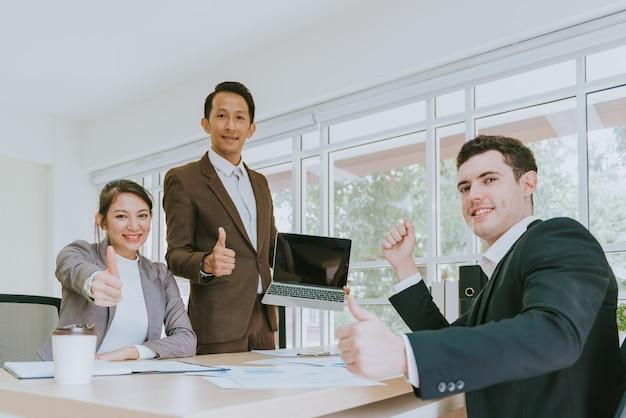 Gens d'affaires heureux montrant les pouces vers le haut Photo Premium
