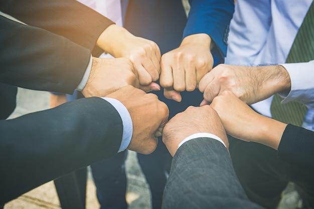 Les gens d'affaires les mains dans les poings dans le concept de cercle, d'affaires et de travail d'équipe Photo Premium
