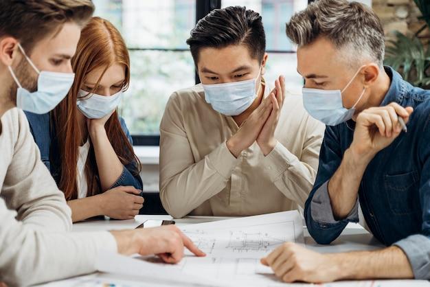 Gens D'affaires Portant Des Masques Médicaux Au Travail Photo gratuit