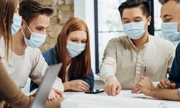Les Gens D'affaires Portant Des Masques Médicaux Tout En Discutant D'un Projet Photo gratuit