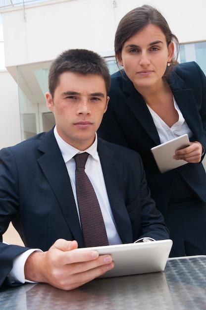 Gens d'affaires sérieux se présentant à la caméra et tenant des tablettes Photo gratuit
