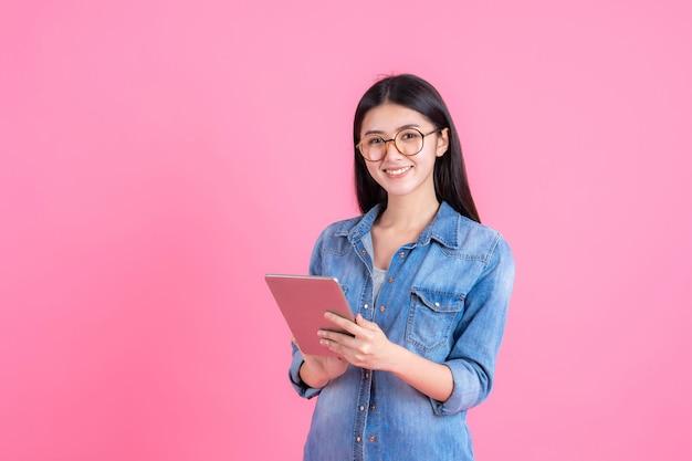 Gens d'affaires de style de vie belle femme jolie fille tenant un ordinateur tablette smartphone sur rose Photo gratuit