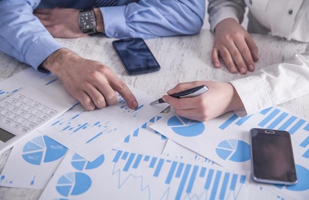 Les Gens D'affaires Travaillant Dans Les Graphiques Financiers. Travailler Au Bureau Photo Premium