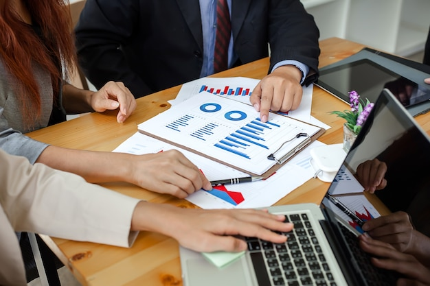 Les Gens D'affaires à Travailler Avec Des Rapports Financiers Et Un Ordinateur Portable. Photo Premium