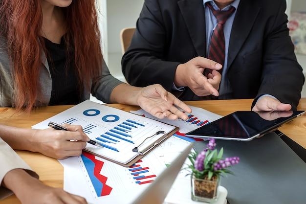 Les Gens D'affaires à Travailler Avec Des Rapports Financiers Et Une Tablette. Photo Premium