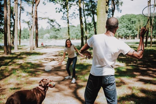 Les gens aiment le badminton au parc playful labrador Photo Premium