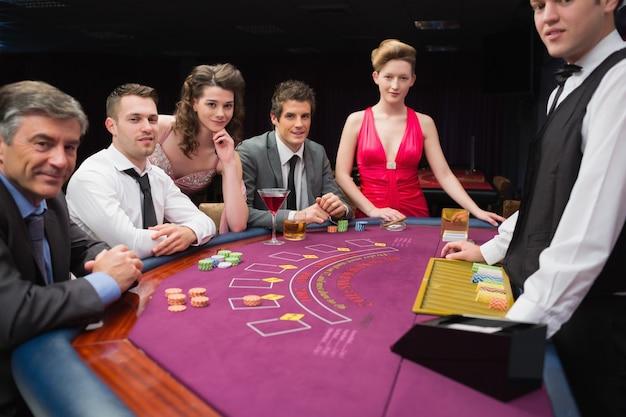 Les gens assis à la table de blackjack, souriant au casino Photo Premium