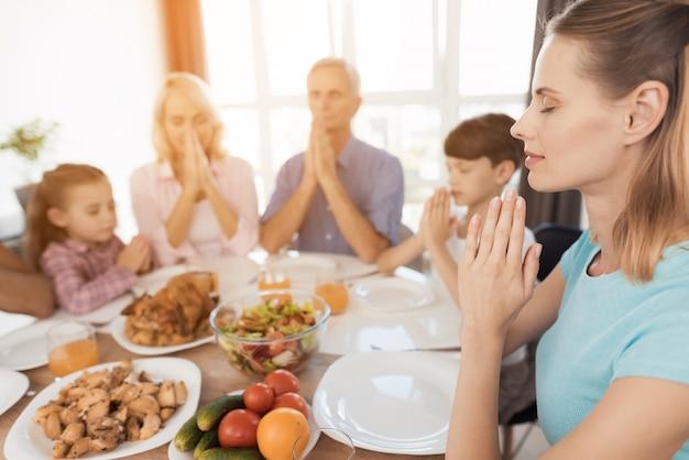 Les gens autour de la table unissent leurs mains et prient. Photo Premium