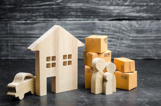Les gens avec des boîtes en carton sont près de la maison. transport de biens et de biens Photo Premium