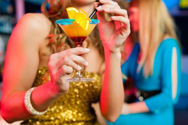 Des gens dans un club ou un bar en train de boire des cocktails Photo Premium