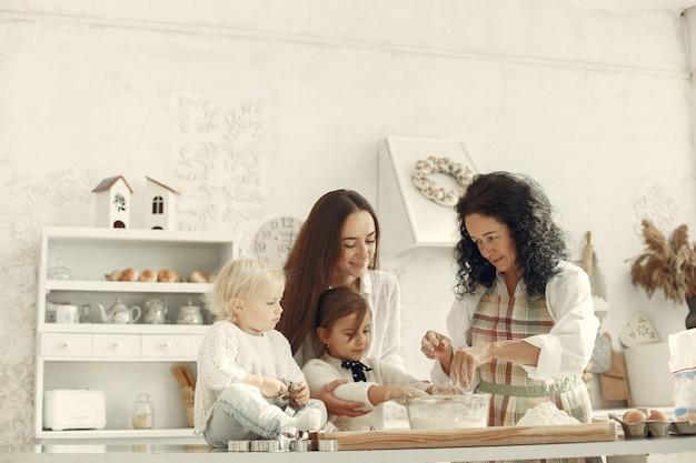 Les Gens Dans Une Cuisine. La Famille Prépare Le Gâteau. Femme Adulte Avec Fille Et Petits-enfants. Photo gratuit