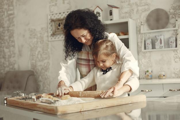 Les Gens Dans Une Cuisine. Grand-mère Avec Petite Fille. Une Femme Adulte Apprend à Cuisiner à Une Petite Fille. Photo gratuit