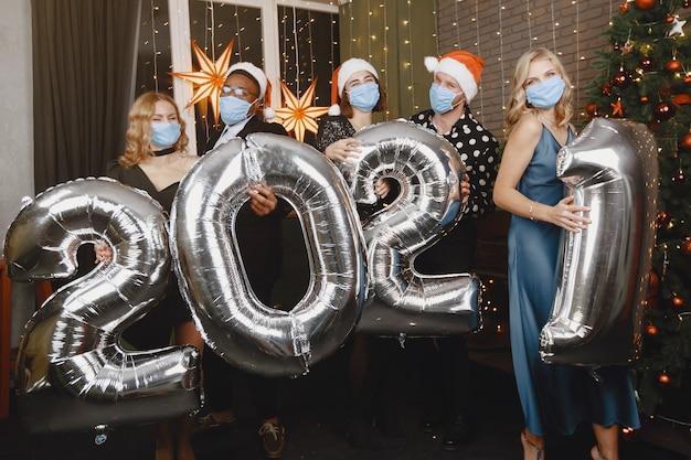 Les Gens Dans Une Décoration Christman. Concept De Coronavirus. Célébrations De Groupe Nouvel An. Les Gens Avec Des Ballons 2021. Photo gratuit