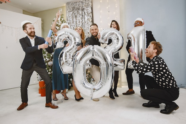 Les Gens Dans Une Décoration De Noël. Homme En Costume Noir. Célébrations De Groupe Nouvel An. Les Gens Avec Des Ballons 2021. Photo gratuit
