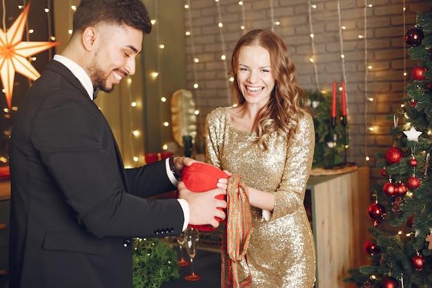 Les Gens Dans Une Décoration De Noël. Homme En Costume Noir. Femme Avec Boîte Rouge. Photo gratuit