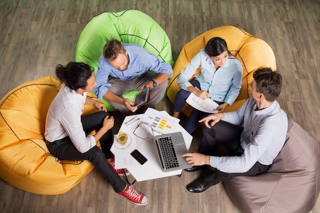 Les gens de discuter des idées et assis au café table Photo gratuit