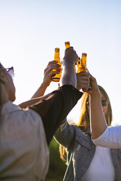 Gens heureux acclamant avec des bouteilles de bière contre le coucher de soleil. jeunes amis détendus se détendre ensemble dans le parc. concept de loisirs Photo gratuit