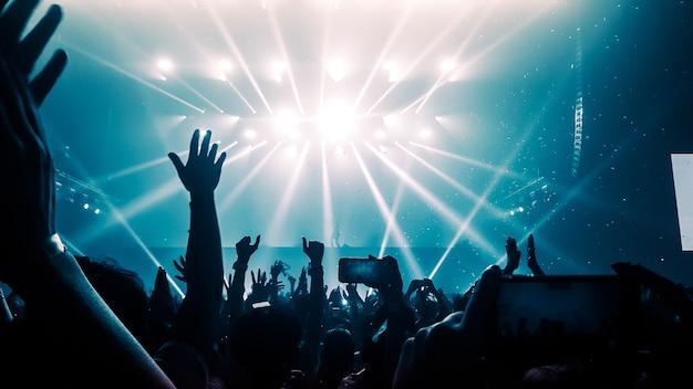 Des gens heureux dansent dans un concert de discothèque Photo Premium