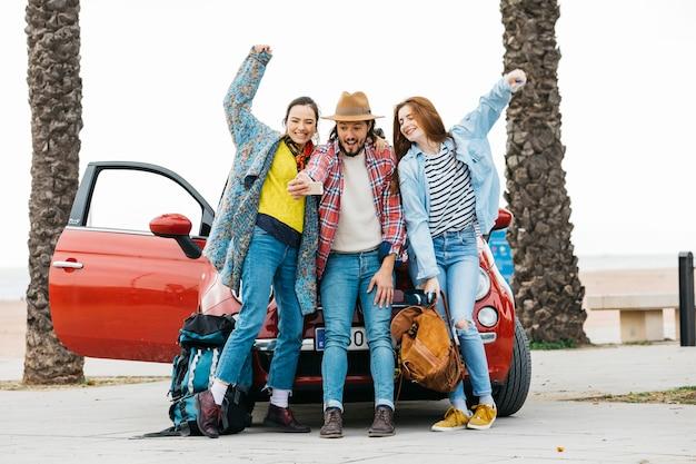 Des gens joyeux prenant selfie près d'une voiture rouge Photo gratuit
