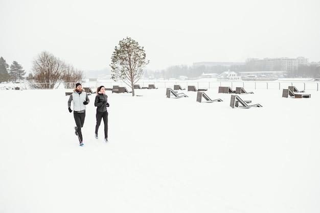 Les Gens De Loin Qui Courent Dans La Nature Pendant L'hiver Photo Premium