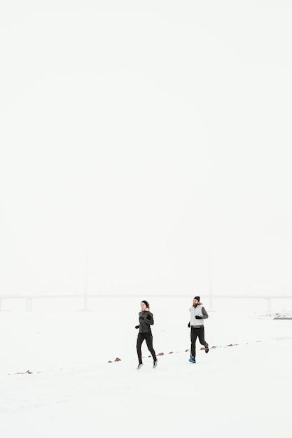 Gens De Loin Qui Courent Dans La Neige Photo Premium