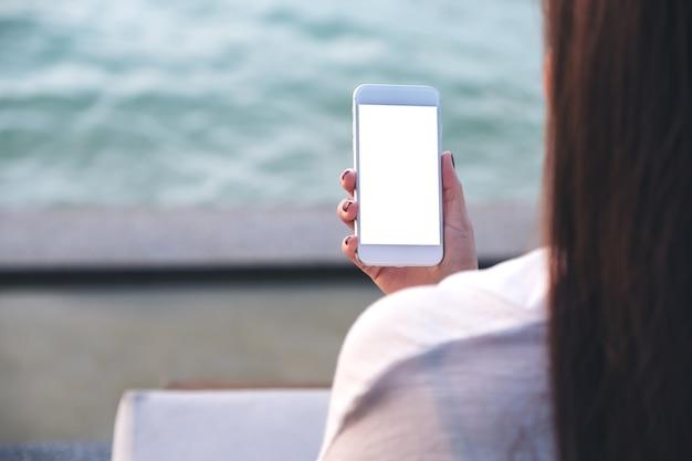 Les gens à la main en utilisant un téléphone intelligent maquette de la mer Photo Premium