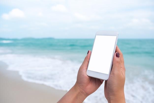 Les gens à la main en utilisant un téléphone intelligent maquette par mer Photo Premium