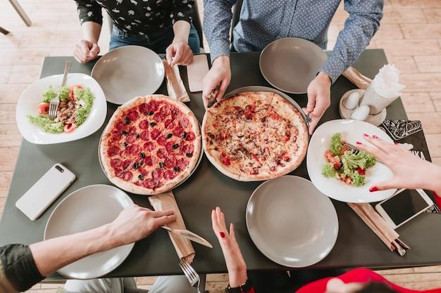 Gens mangeant de la pizza au restaurant Photo gratuit