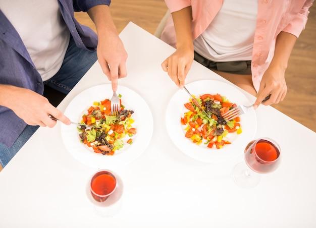 Les gens mangent de la salade dans la cuisine. Photo Premium