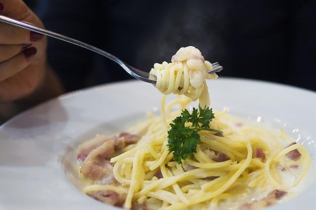 Les gens mangent des spaghettis carbonara Photo gratuit