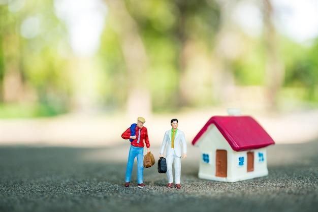 Gens De Miniature, Couple Homme D'affaires Permanent Avec Mini Maison Sur Fond De Nature Verte En Utilisant Comme Bu Photo Premium