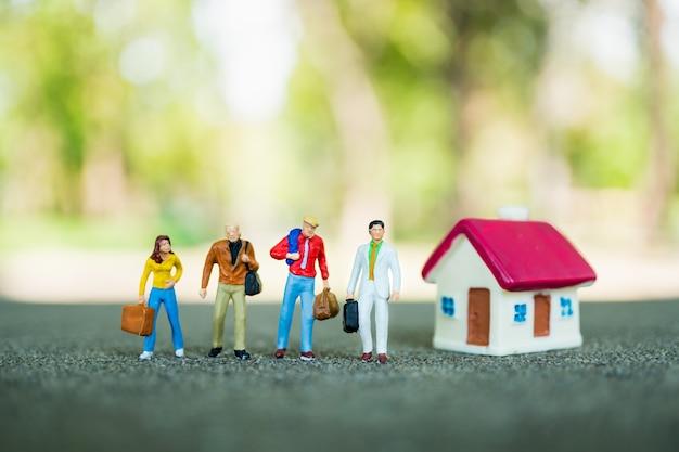 Gens De Miniature, équipe D'homme D'affaires Debout Avec Mini Maison Sur Fond De Nature Verte En Utilisant Comme Busi Photo Premium