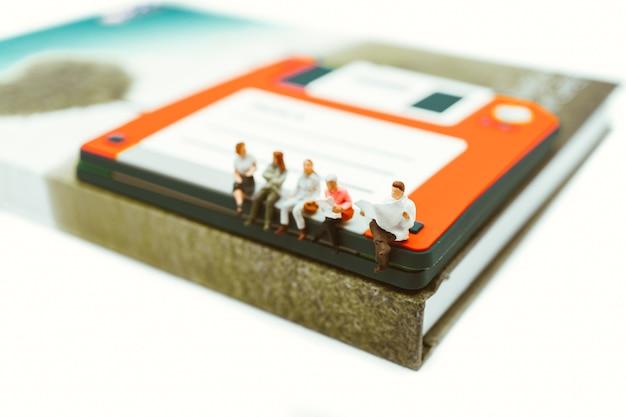 Gens de miniature, homme et femme assis sur le lecteur de disque lisant des journaux en utilisant comme entreprise et educa Photo Premium