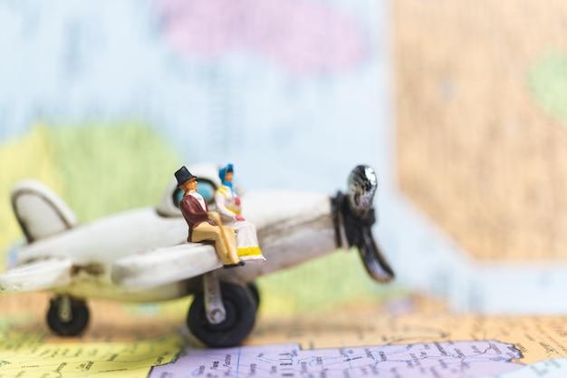 Gens miniatures assis sur l'avion avec fond de carte du monde Photo Premium