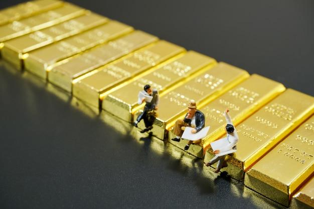 Gens miniatures assis sur une pile de lingots d'or sur fond noir Photo Premium