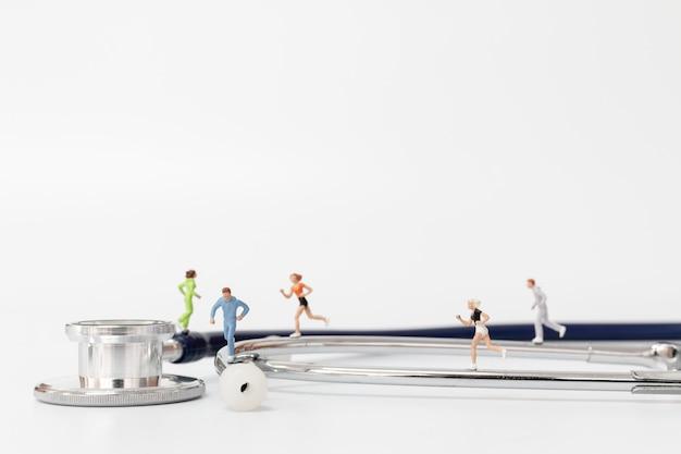 Gens miniatures en cours d'exécution sur le stéthoscope Photo Premium